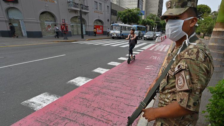 Un soldat contrôle les déplacements de la population péruvienne, appelée à rester chez elle face au coronavirus, à Lima, le 16 mars 2020. (CRIS BOURONCLE / AFP)