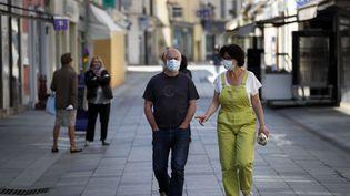 Des piétons avec des masques dans la rue à Sceaux (Hauts-de-Seine), le 8 avril 2020. (THOMAS COEX / AFP)