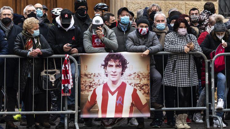 Les supporters rendent hommage au défunt joueur de football italien Paolo Rossi lors de ses funérailles devant la cathédrale Santa Maria Annunciata à Vicenza, dans le nord-est de l'Italie, le 12 décembre 2020. (MARCO BERTORELLO / AFP)