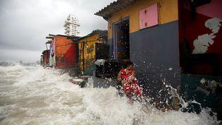 Les vagues éclaboussent une femme devant des maisons côtières lors d'une marée haute à Bombay, en Inde, le 4 juillet 2019. (FRANCIS MASCARENHAS / REUTERS)