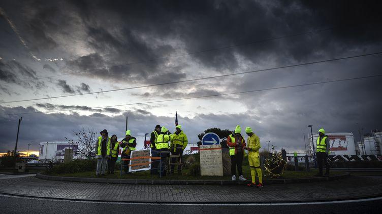 """Des """"gilets jaunes"""" occupent un rond-point près de Lyon, le 17 décembre 2018. (JEAN-PHILIPPE KSIAZEK / AFP)"""
