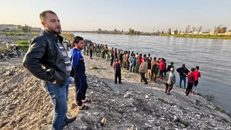 Des personnes observent les opérations de secours, le 21 mars 2019, à Mossoul (Irak), après le naufrage d'un bac sur le Tigre. (ABDULLAH RASHID / ANADOLU AGENCY / AFP)
