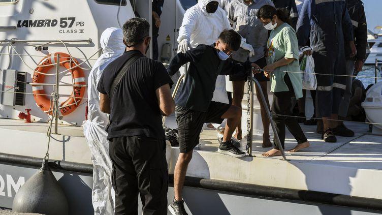 Des migrants débarquent au port de Iérapetra, en Crète (Grèce), le 23 juillet 2021. (JASON TAVLAS / AFP)