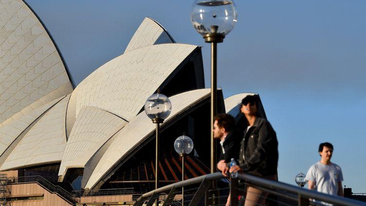 Quelques personnes devant l'opéra de Sydney (Australie), le 14 août 2021. (SAEED KHAN / AFP)