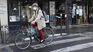 Une femme fait du vélo pendant le confinement, le 30 avril 2020, à Paris. (MEHDI TAAMALLAH / NURPHOTO / AFP)