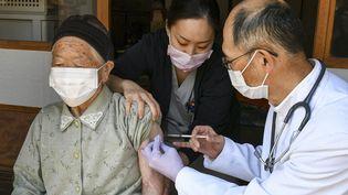 Une personne âgée se fait vacciner contre le Covid-19 au Japon, le 21 avril 2021. (KAZUHIRO NOGI / AFP)