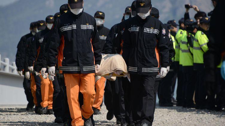 Les secours sud-coréens avec les corps retrouvés dans le ferry naufragé, à Jindo (Corée du Sud), le 20 avril 2014. (ED JONES / AFP)