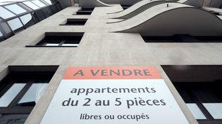 Façade d'immeuble sur laquelle est apposée une annonce de vente de biens mobiliers à Paris. (LIONEL BONAVENTURE / AFP)