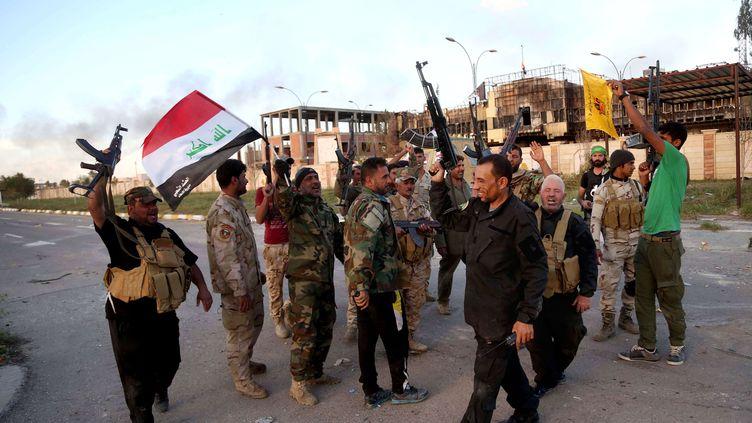 Des militaires irakiens et des miliciens chiites fêtent la victoire à Tikrit (Irak), le 31 mars 2015. (KHALID MOHAMMED / AP / SIPA )