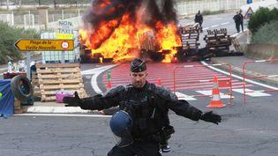 """Un gendarme empêche l'accès à une barricade en feu, pendant que ses collègues dispersent les """"gilets jaunes"""" qui bloquent le dépôt de pétrole dePort-La-Nouvelle (Aude), le 20 novembre 2018. (RAYMOND ROIG / AFP)"""