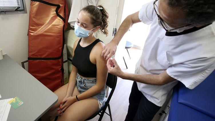 Une adolescente se fait vacciner en Corse, le 22 juillet 2021. (PASCAL POCHARD-CASABIANCA / AFP)