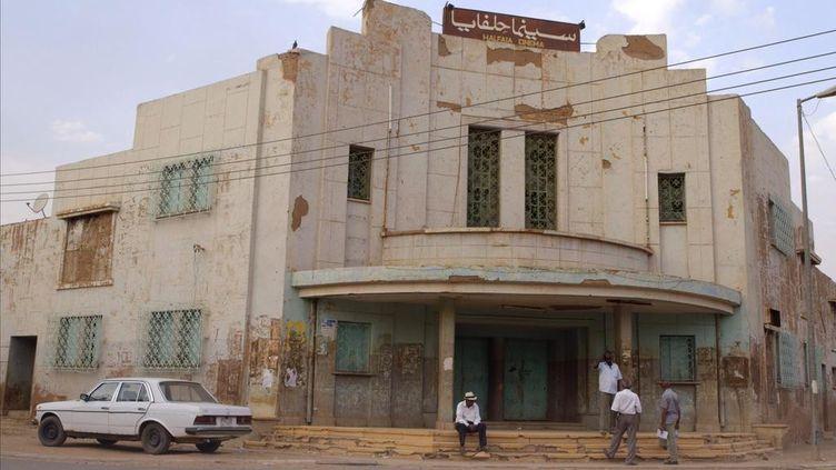 """Les cinéastes soudanais Manar Al Hilo,Ibrahim ShadadSuleiman, Mohamed IbrahimetAltayeb Mahdi, devant le cinéma """"La Revolution"""" à Khartoum, la capitale soudanaise. (AGAT FILMS &CIE / EX NIHILO)"""