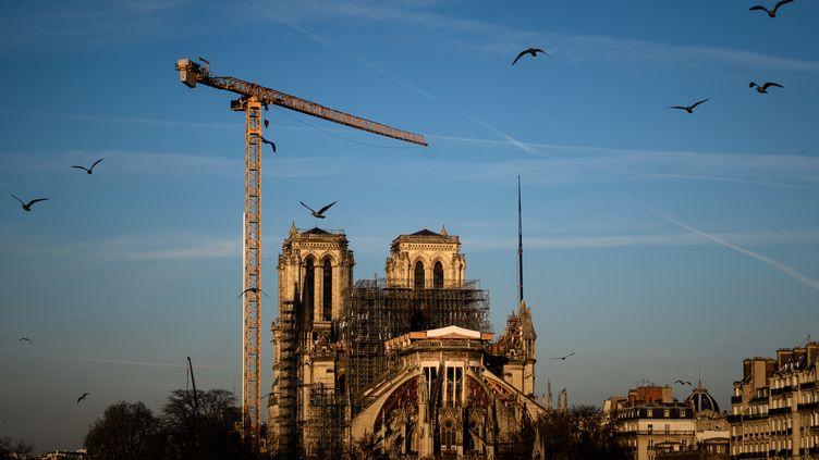 Notre-Dame de Paris, surmontée d'une grue à l'arrêt et toujours enserrée dans son échaffaudage, un an après l'incendie du 15 avril 2019. (PHILIPPE LOPEZ / AFP)