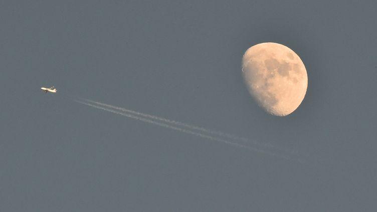 Un avion passe devant la Lune dans le ciel de Cermis (Italie) le 8 janvier 2017. (GIUSEPPE CACACE / AFP)