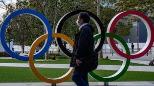 Un passant longe une structure dédiée aux Jeux olympiques de Tokyo (Japon), le 11 mars 2020. (PHILIP FONG / AFP)
