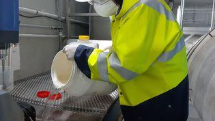 Un employé de lastation d'épuration de Colombes, dans les Hauts-de-Seine, manipule de l'eau usée après filtration. (SOLENNE LE HEN / RADIO FRANCE)