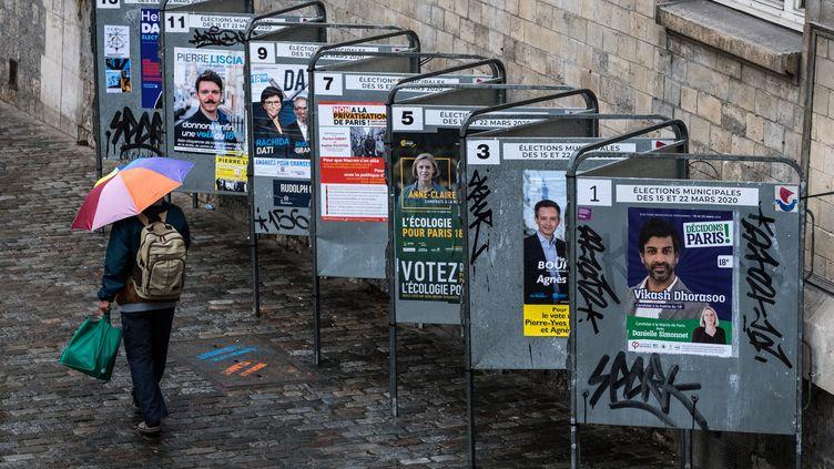 Un homme dépasse en marchant une série d'affiches de campagne électorale, le 14 mars 2020, à Paris. (JOEL SAGET / AFP)