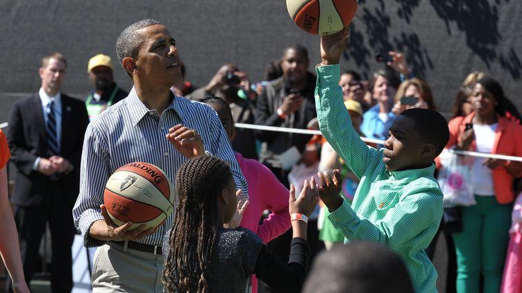 Barack Obamajoue au basket avec des enfants le 1er avril 2013 sur la pelouse sud de la Maison Blanche à Washington (Etats-Unis). (MANDEL NGAN / AFP)
