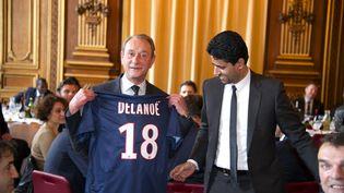 Bertrand Delanoë pose avec un maillot du PSG en compagnie du président du club,Nasser Al-Khelaifi, le 30 janvier 2013 à Paris. (LIONEL BONAVENTURE / AFP)