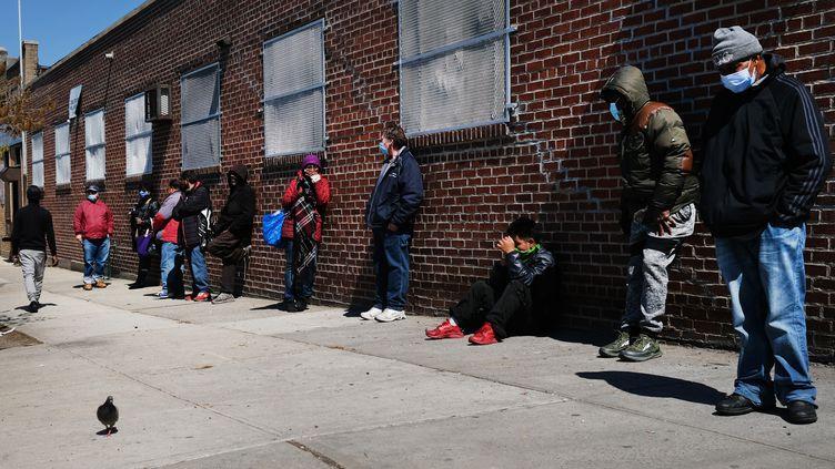 Des Américains font la queue à l'entrée d'une banque alimentaire, le 28 avril 2020, à New-York. (SPENCER PLATT / GETTY IMAGES NORTH AMERICA / AFP)