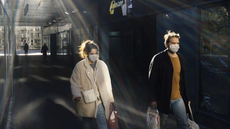 Une femme et un homme rentrent chez eux après avoir fait des courses, le 24 mars 2020, à Paris. (DENIS MEYER / HANS LUCAS / AFP)