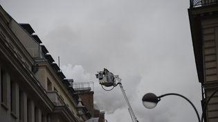 Des pompiers éteignent l'incendie de la toiture de l'hôtel Ritz à Paris, le 19 janvier 2016. (LIONEL BONAVENTURE / AFP)