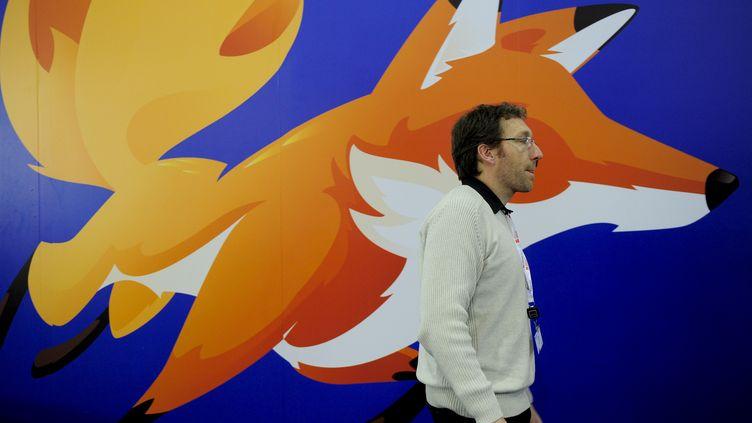 Un homme passe devant une affiche de Mozilla Firefox, le 27 février 2013, au Mobile World Congress de Barcelone (Espagne). (JOSEP LAGO / AFP)