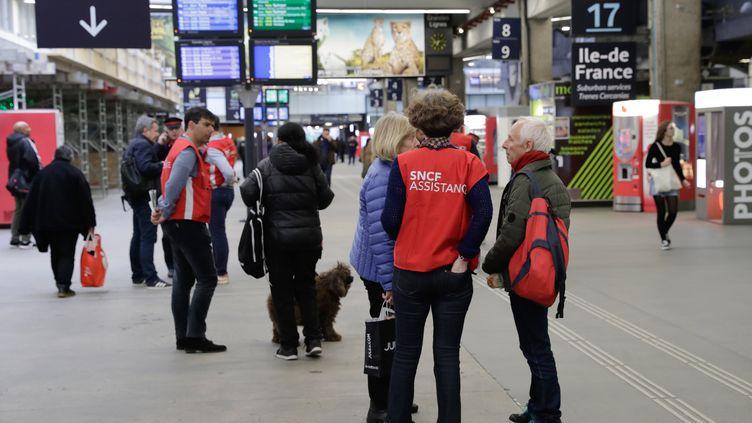 Des employés aident les usagers de la gare Montparnasse, le 8 avril 2018 à Paris. (THOMAS SAMSON / AFP)