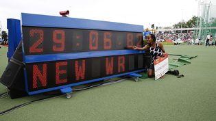 Sifan Hassan pose à côté de son novueau record du modne du 10 000m, le 6 juin 2021. (VINCENT JANNINK / ANP)