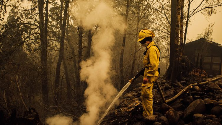 Un pompier américain éteint les braises d'un incendie dans l'Ouest des Etats-Unis, le 10 septembre 2020 (photo d'illustration). (KATHRYN ELSESSER / AFP)