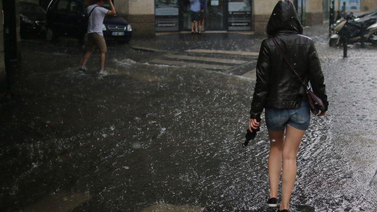 Des passants sous la pluie lors d'un orage à Nantes (Loire-Atlantique), le 9 juillet 2017. (MAXPPP)