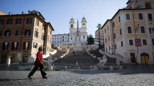Une femme traverse la Piazza di Spagna à Rome, dimanche 15 mars 2020 à Rome (Italie). (CHRISTIAN MINELLI / NURPHOTO / AFP)