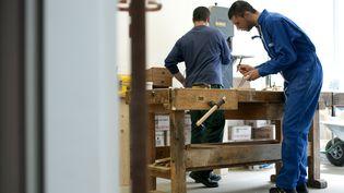 Un mineur délinquant travaille avec un agent technique, le 18 mai 2009, dans la menuiserie du centre éducatif fermé de Mulhouse (Haut-Rhin). (SEBASTIEN BOZON / AFP)
