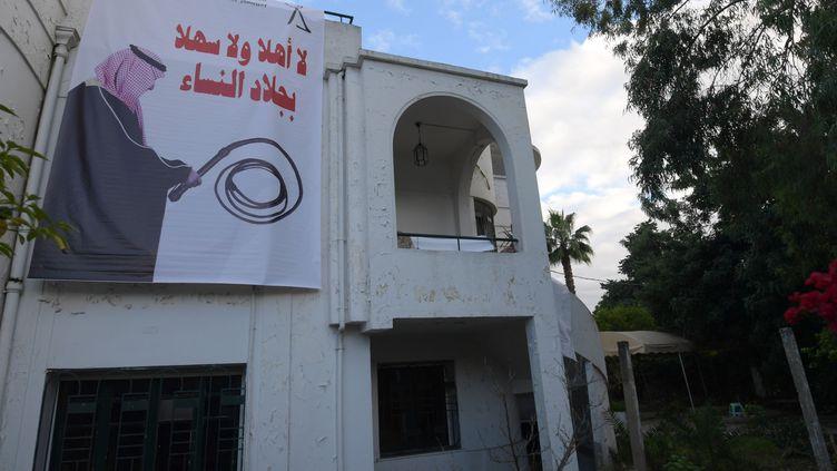 """La photo prise le 26 novembre 2018 montre une bannière suspendue au siège de l'Association des Femmes Démocrates Tunisiennes dans la capitale Tunis, montrant le prince héritier saoudien Mohammed bin Salman tenant un fouet avec une légende en arabeaffirmant """"le bourreau, n'est pas le bienvenu"""". (FETHI BELAID / AFP)"""