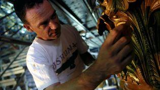 Un doreur travaille sur la rénovation de l'opéra de Paris, le 2 décembre 2003 (illustration). (MAXPPP)