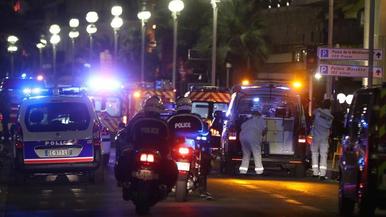 Des officiers de police et des secours arrivent sur la scène de l'attaque, jeudi 14 juillet 2016, sur la promenade des Anglais à Nice (Alpes-Maritimes). (VALERY HACHE / AFP)