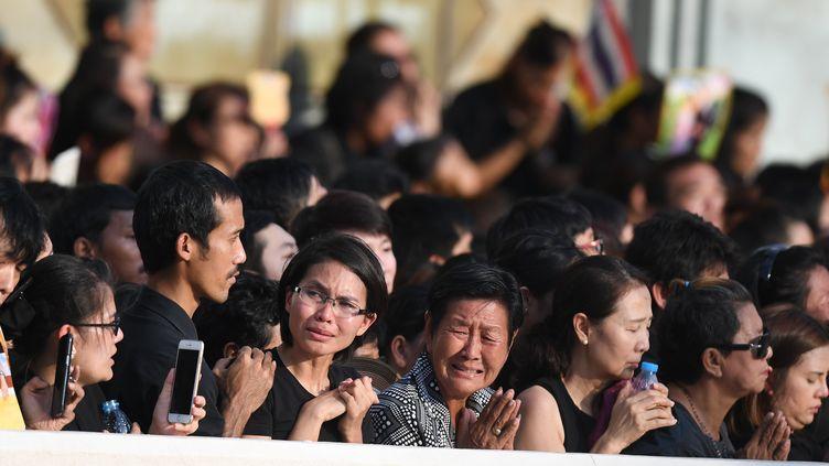 Des Thaïlandais sur lepassage du cortège funéraire du roi Bhumibol Adulyadej, vendredi 14octobre à Bangkok. (MANAN VATSYAYANA / AFP)