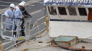 """Des enquêteurs s'affairent au-dessus de l'épave du chalutier """"Bugaled Breizh"""", le 15 juillet 2004, à Brest (Finistère). (MARCEL MOCHET / AFP)"""
