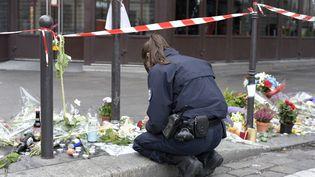 Une policièrese recueille devant le café La Bonne Bière, le 14 novembre, à Paris, au lendemain des attentats. (ADRIEN MORLENT / AFP)