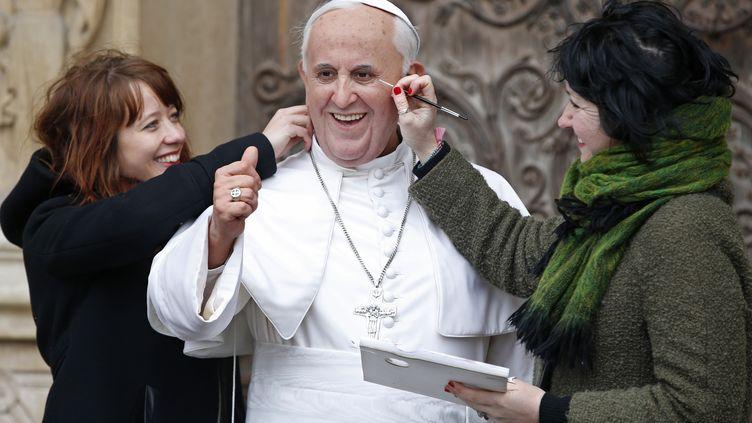 Deuxartistes du musée Grévin posent à côté du pape François devant la cathédrale Notre-Dame-de-Paris, le 2 avril 2015. (CHARLES PLATIAU / REUTERS )