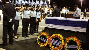 Des policiers israéliens saluent le cercueil de l'ancien président Shimon Peres, le 29 septembre 2016, à Jérusalem. (GALI TIBBON / AFP)