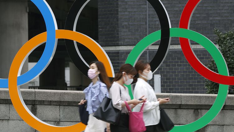 Des femmes devant les anneaux olympiques à Tokyo (Japon), jeudi 8 juillet 2021. (SHINJI KITA / KYODO NEWS / AFP)