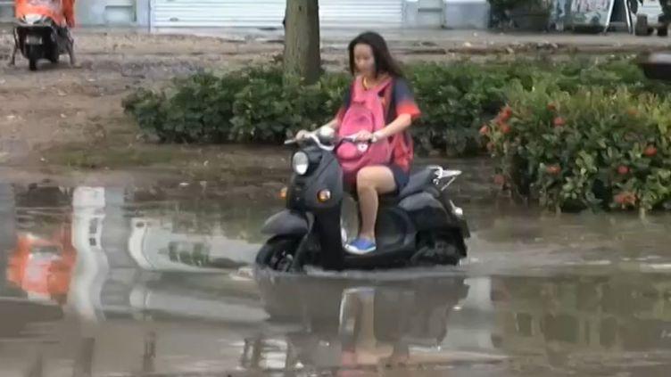 Une habitante de la ville deBeihai (province du Guangxi) tente de circuler sur son scooter dans une rue inondée, dimanche 26 juillet 2015. (APTN)