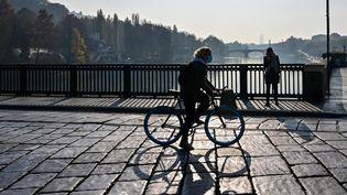 Une femme traverse à vélo le pont Vittorio Emanuele I dans le centre-ville de Turin, pendant la pandémie de Covid-19, le 17 novembre 2020. (MIGUEL MEDINA / AFP)
