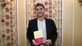 Laurent Binet pose avec son livre, après la remise du prix Interallié, à Paris, le 12 novembre 2015. (PATRICK KOVARIK / AFP)