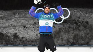 Martin Fourcade saute du podium après sa victoire en poursuite aux JO d'hiver de Pyeongchang (Corée du Sud), le 12 février 2018. (FRANCK FIFE / AFP)