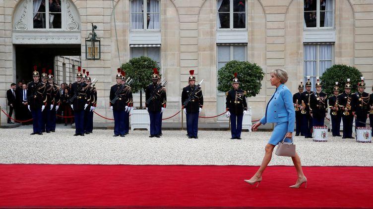 Vêtue d'un tailleur bleu dessiné par Nicolas Gesquière pour Louis Vuitton, la Première Dame, Brigitte Macron, fait son entrée dans la cour de l'Elysée, avant son mari. (CHRISTIAN HARTMANN / REUTERS)