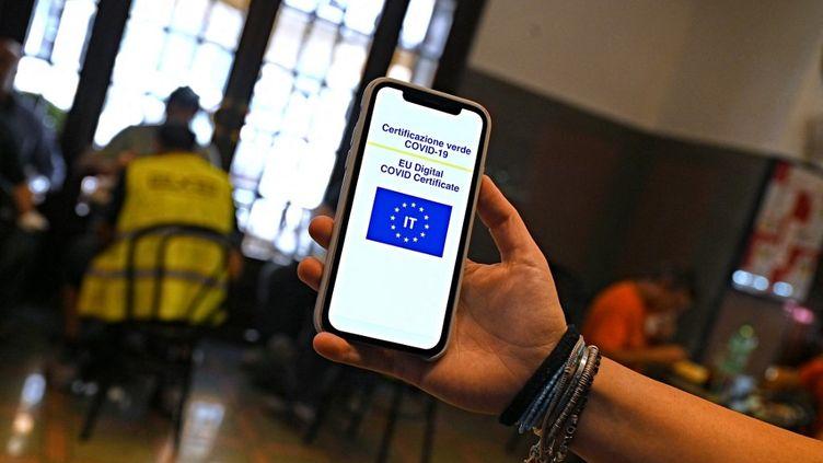 """Un client montre son """"green pass"""", le 6 août 2021 dans un bar de Rome (Italie). (ANDREAS SOLARO / AFP)"""
