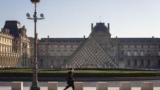 Un passant devant la pyramide du Louvres et une esplanade déserte en novembre 2020. (EMMA BUONCRISTIANI / HANS LUCAS)