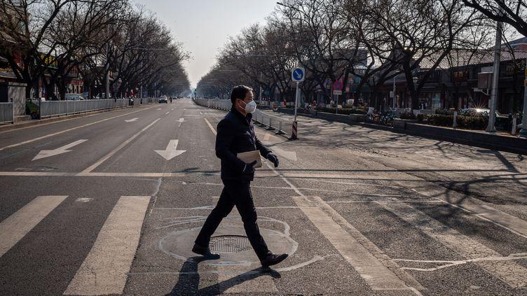 Un homme portant un masque respiratoire à Pékin le 23 février 2020 (NICOLAS ASFOURI / AFP)